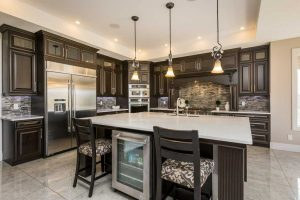 Kitchen with white ceiling and white marble floor; dark maple cabinets; island with with countertop, sink and mini-fridge