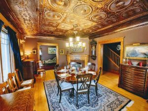 Interior dining room with wood floor and walls, and decorative ceiling panels above; circular wood table with six wood chairs around, on top of navy and white pattern rug; wood cabinets on the right and left, fireplace on back wall