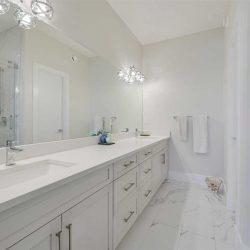White bathroom, two sinks, bright lights.