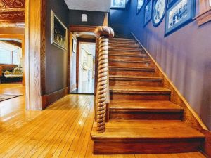 Interior entrance looking at hand-crafted wood stairs with a spiral post railing at the bottom; hardwood flooring leading to kitchen straight ahead, and to living room on the left
