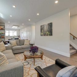 Living room, white walls, grey couches, wood wining table.