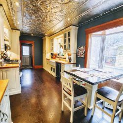 Interior kitchen with dark wood floor, blue walls, white cabinets and decorative ceiling panels above; white and black kitchen table and chairs next to window cubby