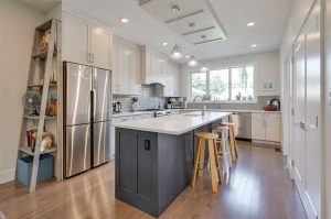 Kitchen, steel fridge, L-shaped counter, large window.