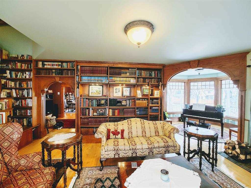 Interior living room with hardwood floor and light green plaster ceiling; light beige couch in middle, single red patter chair on left, small tables on either side; back and left walls just packed with books; piano in the nook to the right