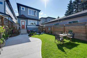 Bright backyard, green grass, winding sidewalk, wood table, steel chairs.