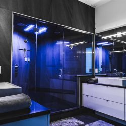 Black and white bathroom with shower that lights up blue