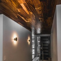 Front entrance hallway with white walls and a freakin' hardwood ceiling leading to black door