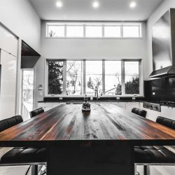 Dark wood table in centre of white kitchen with black appliances on left and right; looks out large windows in background