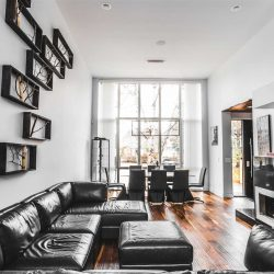 White living room facing out through floor-to-ceiling windows, hardwood floors; black sectional on left with framed tree branches above; fireplace on right