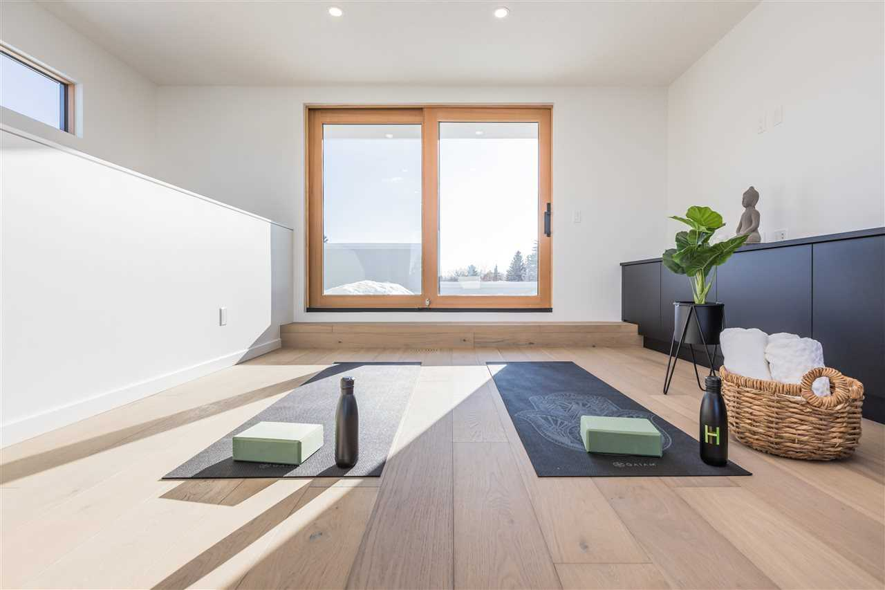 Interior loft looking out to patio through light-wood framed doors; white oak floor with two black yoga mats; white ceiling and walls; green plant on the right in front of black cabinets