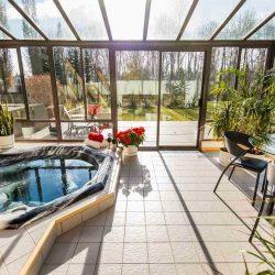 Sunroom with black-framed windows, light tiles, plants and a hot tub
