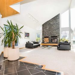 White-walled living room with light carpet and dark grey furniture. Giant windows and fireplace on triangular wall.