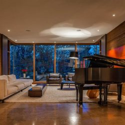 Interior living music room, brown marble floor and wood walls, white ceiling; grand piano to right with a guitar sitting on the other side; white cloth couch on left, two leather chairs centre, white shag carpet in the middle; floor-to-ceiling windows in background