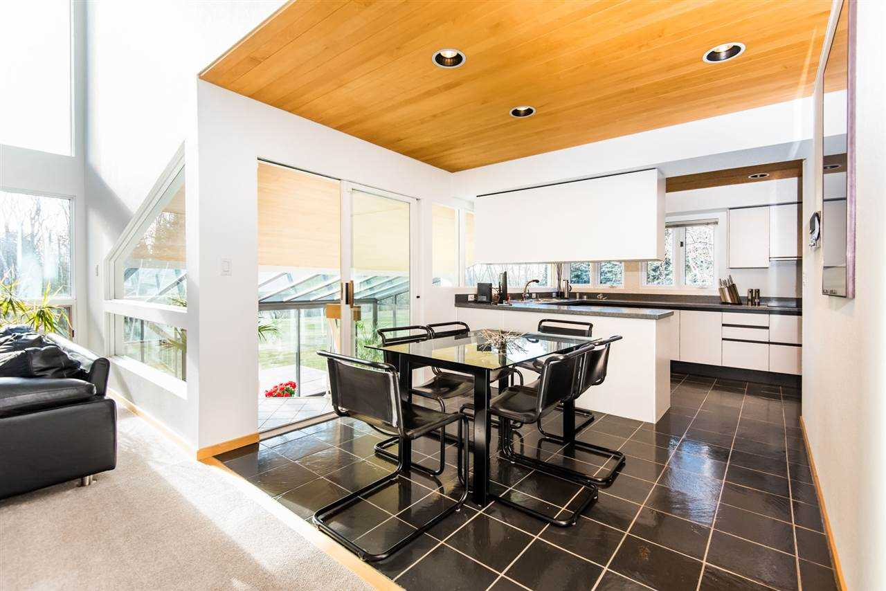 White-walled kitchen with wood ceiling and black tile floor; black dining table and chairs; white island and cabinets