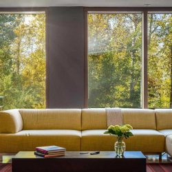 Living room with light grey tile floor; yellow couch sits behind wood coffee table on rd rug; floor-to-ceiling, wood-framed windows  look out to trees