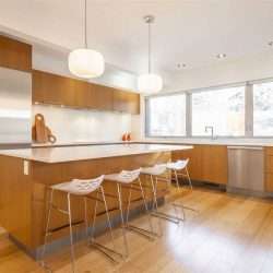 Interior kitchen, hardwood floor and cabinets, white countertops; four silver and white stools at island, two white lights overhead; windows on right