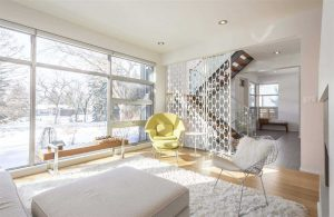 Interior all-white living room, looking out front window; white footrest and chair on top of white shag carpet on top of hardwood floor; yellow chair in middle of the shot; circular-holed divider between room and two-flight stairs