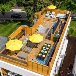 All-wood rectangular rooftop patio; black table on blue rug with eight black chairs and eight yellow dinner plates bottom right; two yellow umbrellas with grey furniture to the left; stainless steel outdoor kitchen middle-right; hot tub top right next two another yellow umbrella and two chaise loungers