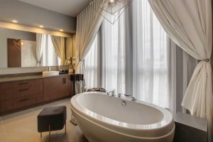 En suite bathroom with free-standing soaker tub, black stool, wood cabinets and drawers under a large mirror; curtains over the windows.