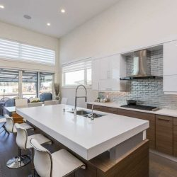 Kitchen with hardwood floor and white counters, upper cabinets and walls, wood cabinets below; tiered island with white counter and wood bottom, three white chairs and a sink