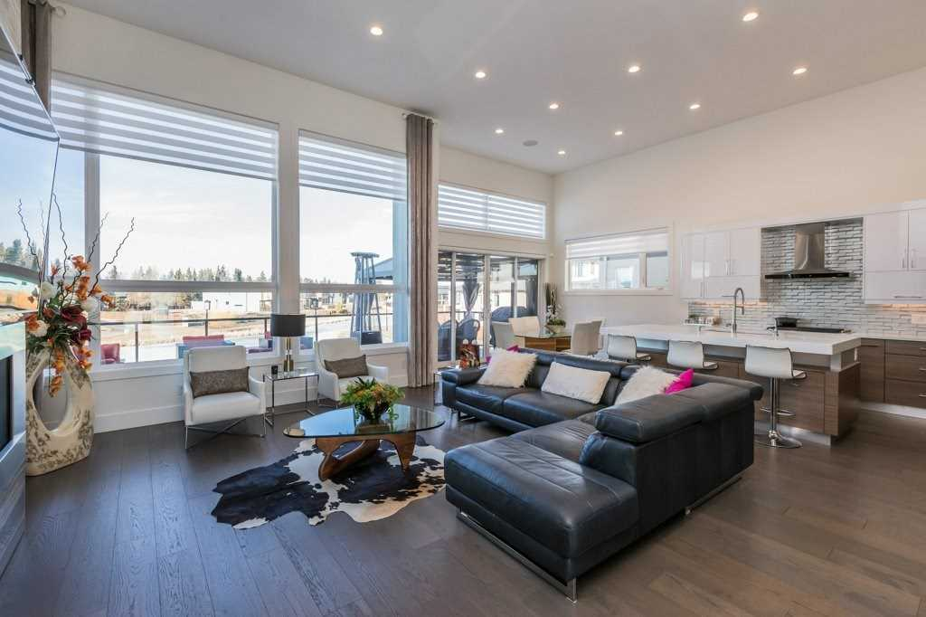 Interior living/dining area with hardwood floor and white walls; black sectional couch in the middle and two white chairs by the windows; cow-pattern rug under glass coffee table; kitchen in background