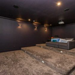 Theatre room with dark grey carpet and purple walls; projector hangs above deep couch which sits on third level of the terraced floor; large screen on the left