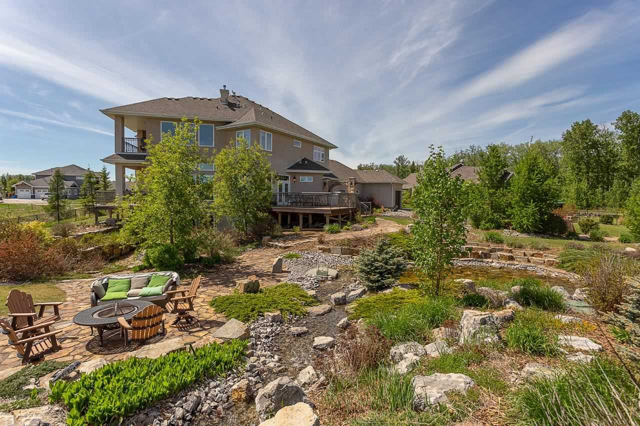 Backyard creek surrounded by rocks and green bushes and trees; stone path leading to fire pit surrounded by four wood chairs and plastic bench with grey and green cushions; two story beige house in background
