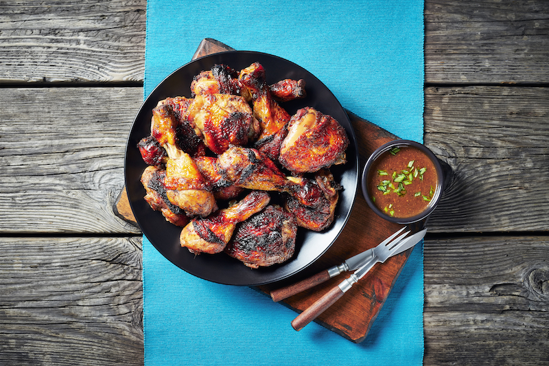 Jerk,Chicken,On,A,Black,Plate,On,A,Table,Mat