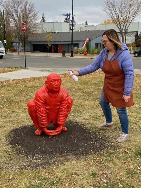 A woman spray painting a statue of a man squatting down