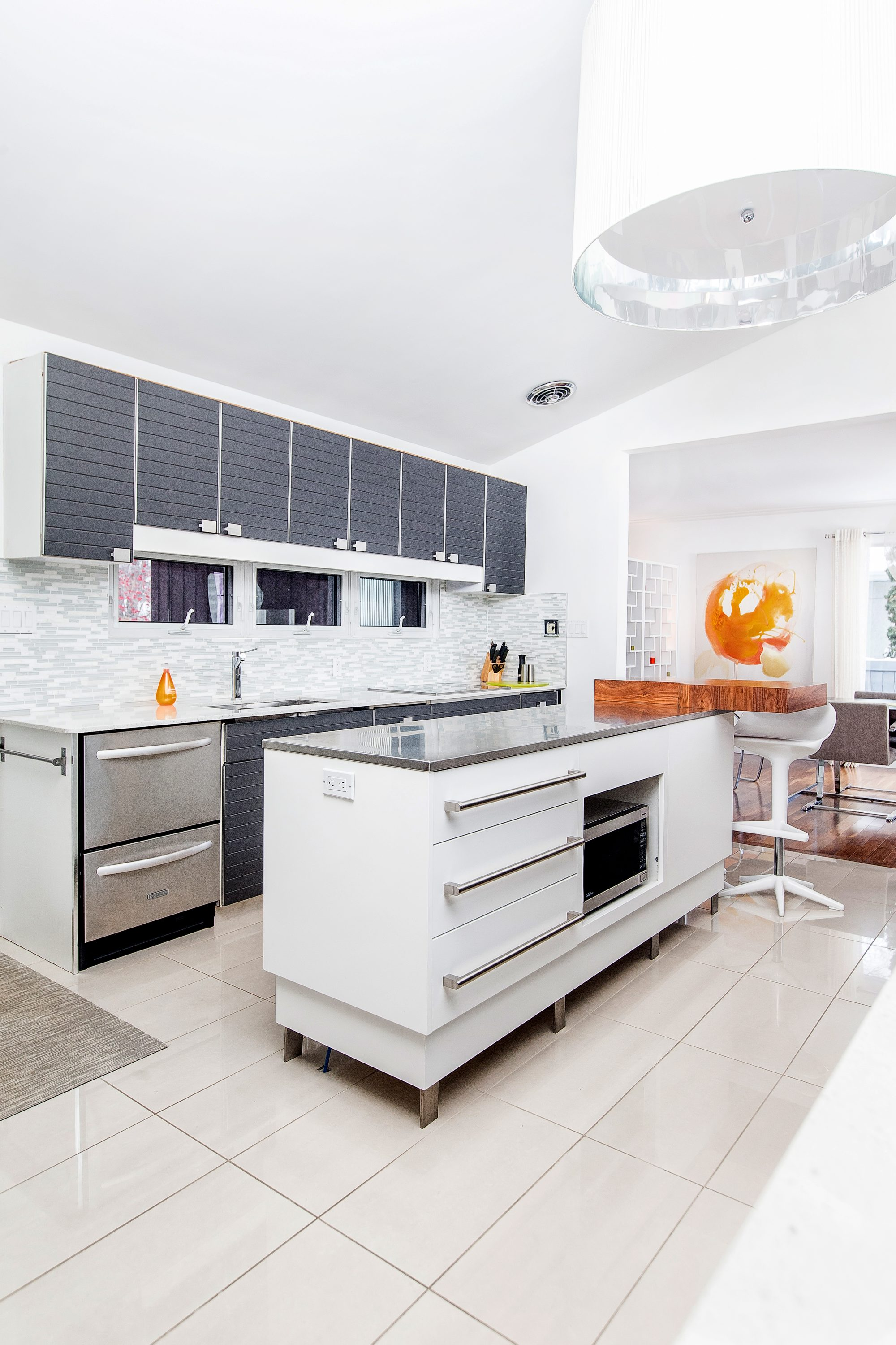 Kitchen:  Painting by Annique Shields.  Kartell chair and Chilewich mat, from Inspired Home Interiors.  Custom-made island by IZM.  Global Views vase and Gus Modern cube, both from Inspired Home Interiors.  Light from Vivid Concepts Lighting + Design.
