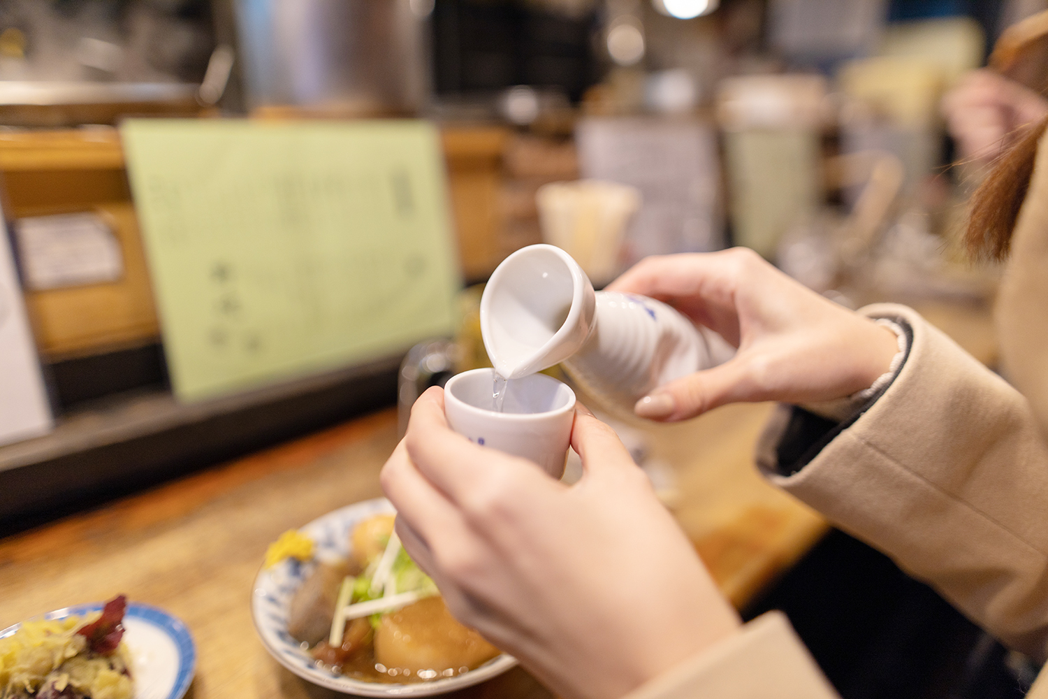Young woman drinking Japanese Saki at Izakaya bar counter